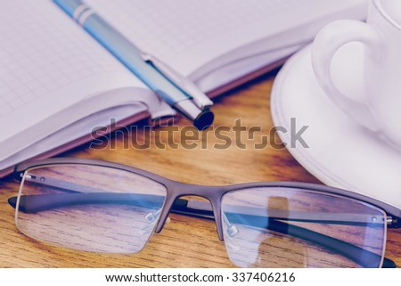 glasses pen on the table and pads - stock photo