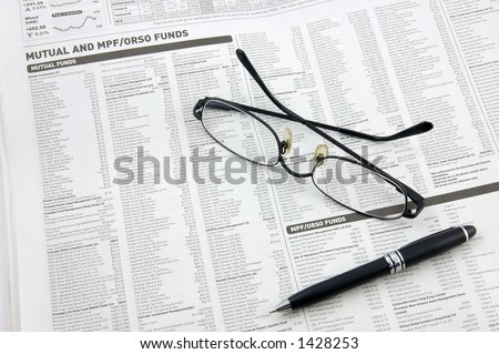 Glasses, pen over mutual funds data on newspaper - stock photo