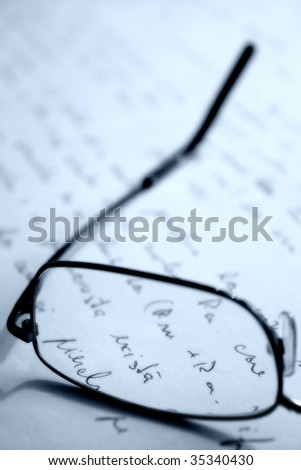 Glasses placed on a sheet of hand written paper - stock photo