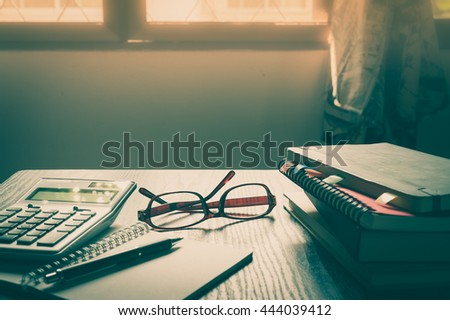 Glasses put down on table beside notebooks and pen in morning time on work day. Freelance business working concept with vintage filter effect