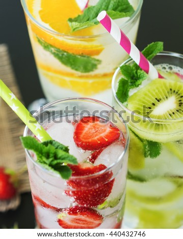 Glasses with a refreshing lemonade with fresh strawberries, kiwi, orange, mint and ice. Close-up.