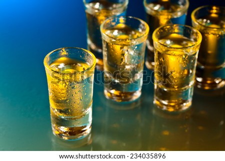 Glasses with an alcoholic drink on a glass table - stock photo