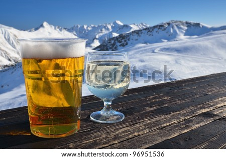 Glasses with beer and white wine on a wooden table in high mountain cafe. Shallow depth of field. - stock photo
