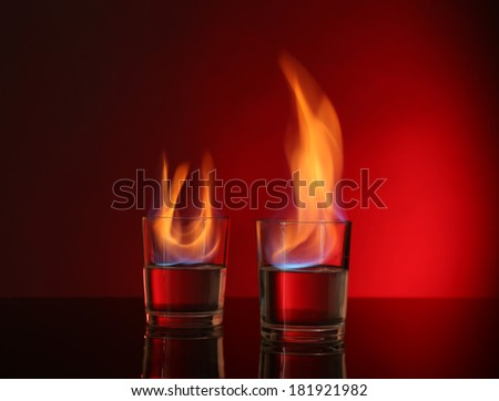Glasses with burning alcohol on red background - stock photo