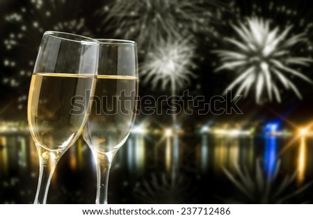 Glasses with champagne against fireworks and city lights - stock photo