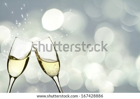 Glasses with champagne against holiday lights  - stock photo