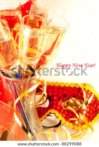 Glasses with champagne and a New Year's mask, a carnival