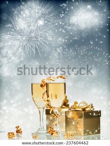 Glasses with champagne and gift box over sparkling holiday background - stock photo