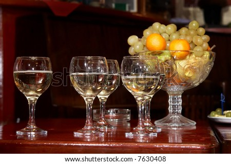 Glasses with champagne and vase with fruits