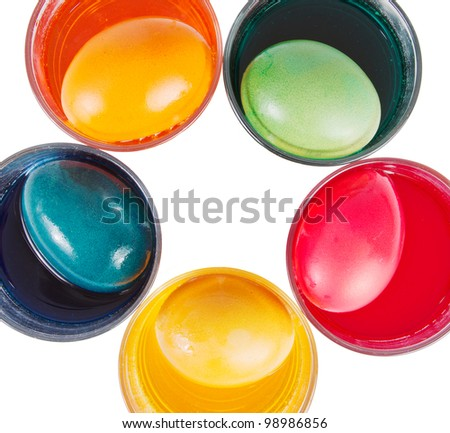 Glasses with different dyed Easter eggs over a white background