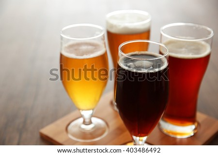Glasses with different sorts of craft beer on wooden tray - stock photo