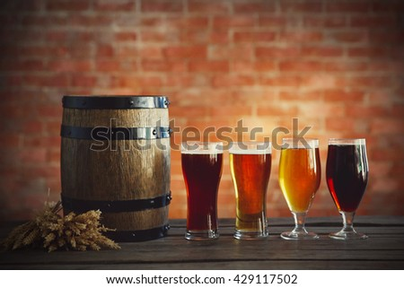 Glasses with different sorts of craft beer, wooden barrel and barley. Retro stylization - stock photo