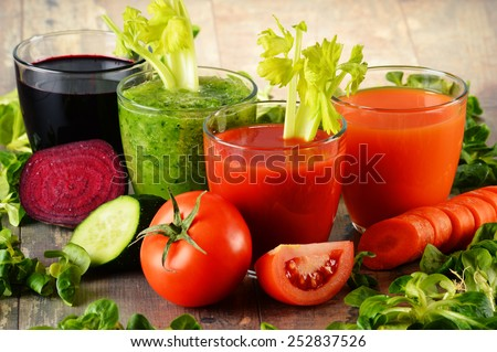 Glasses with fresh organic vegetable juices on wooden table. Detox diet - stock photo