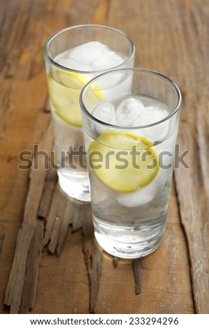 Glasses with ice cubes on wooden table - stock photo