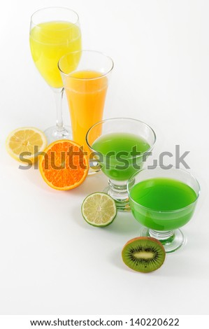 glasses with juices of citric fruit and halves of fruits