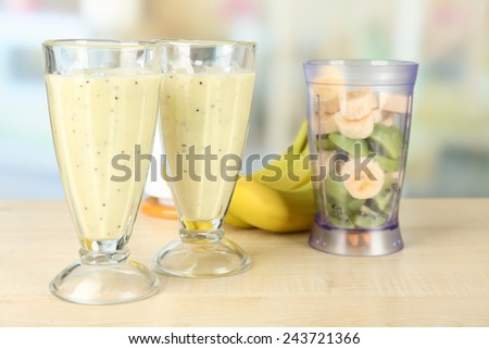 Glasses with milkshake and sliced fruits in bowl of blender on wooden table, on bright background