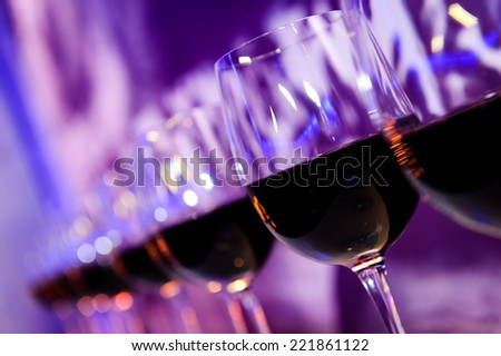 Glasses with red wine lit by nightclub lights on dark-purple background