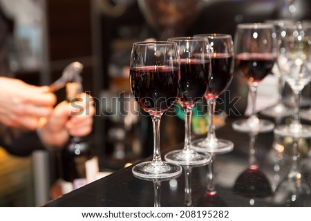 glasses with red wine on bar counter - stock photo