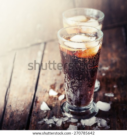 Glasses with soft drink on wooden background - stock photo