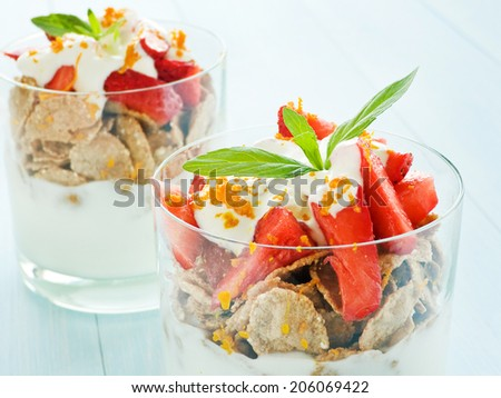 Glasses with strawberry parfait on the blue background. Shallow dof.