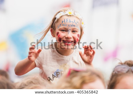 Glastonbury, Somerset, UK - June 27, 2015 - Young festival goer enjoying Lionel Richie playing Glastonbury Festival's Pyramid Stage - stock photo