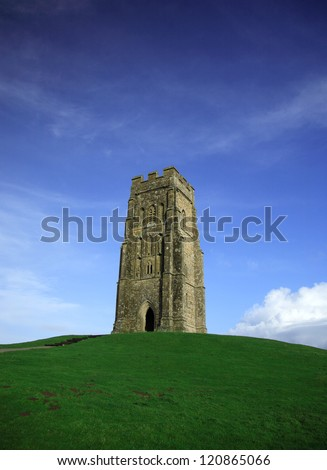 Glastonbury Tor against a vivid blue sky and green grass - stock photo