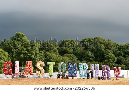 GLASTONBURY, UK - JUNE 28: Festival goers look at a panorama over the festival with a large Glastonbury sign at Glastonbury Festival on 28th June, 2014 at Pilton Farm, Somerset. - stock photo