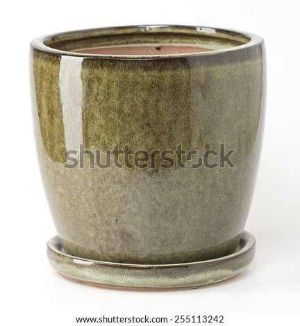 Glazed green ceramic flowerpot with saucer on white