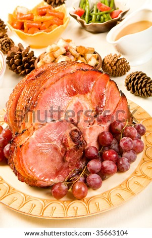 Glazed Spiral Sliced Ham garnished with red globe grapes - stock photo