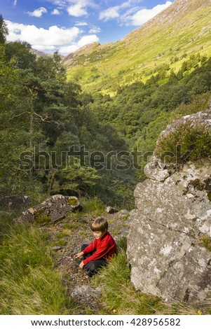 GLEN NEVIS, SCOTLAND - AUGUST 22, 2004: Boy rests on hiking trail in Glen Nevis, near Fort William in the Highlands. - stock photo