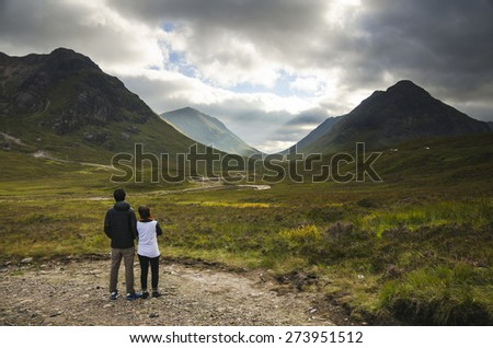 Glencoe in the Highlands of Scotland, scene of the historic 1692 massacre. The old road meanders between rocky mountain slopes across moorland covered with wild flowers and purple heather. - stock photo