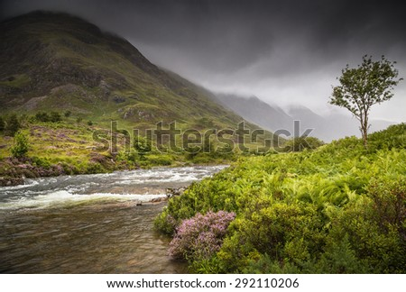 Glencoe, Scotland. Scottish landscape, with a river on the foreground and a mountain on the background, surrounded by clouds. - stock photo