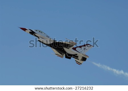"""GLENDALE, AZ - MARCH 21: A U.S. Air Force Thunderbird F-16 performs at the biennial air show (""""Thunder in the Desert"""") at Luke Air Force Base on March 21, 2009 in Glendale, AZ. - stock photo"""