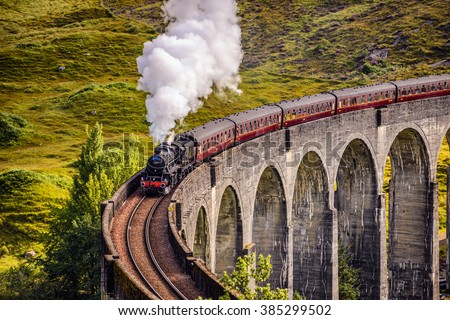 GLENFINNAN, SCOTLAND - SEPTEMBER 9, 2015 : Glenfinnan Railway Viaduct in Scotland with the Jacobite steam train passing over - stock photo