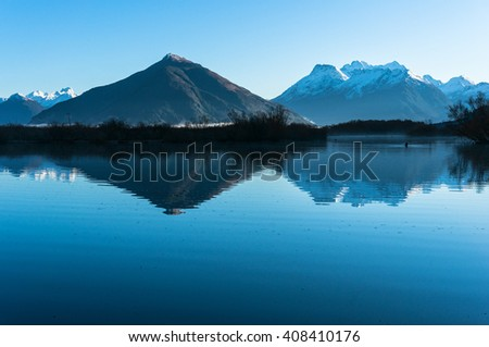Glenorchy lagoon landscape with snow covered mountains reflected in lagoon water. Winter mountain landscape with frozen lake and yellow flowers. South Island, New Zealand - stock photo