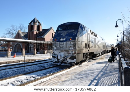 GLENVIEW, IL, USA - DECEMBER 13, 2010: Passengers waiting to board an Amtrak train at Glenview station. Amtrak provides intercity passenger train service in the US. - stock photo