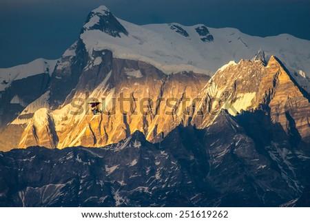 glider flying at sunset Himalaya mountains, Nepal. - stock photo