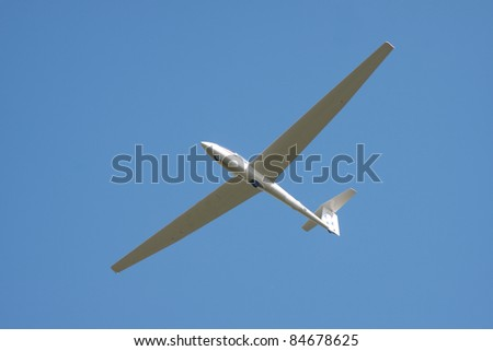 Glider isolated against blue sky - stock photo