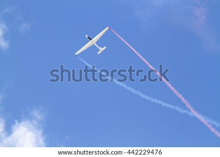 Glider performing aerobatics with smoke trails at airshow on sunny day - stock photo