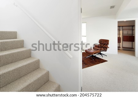 Glimpse from stairway of relaxing brown chair in modern town home - loft - stock photo