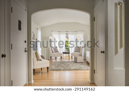 Glimpse into amazing bright and harmonic Living Room Interior with white couch, chair, fire place, beautiful inlaid hardwood floor, arched niches and grey handwoven rug. - stock photo