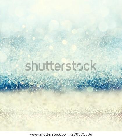 glitter vintage lights background with light burst . gold, blue and white. de-focused.  - stock photo