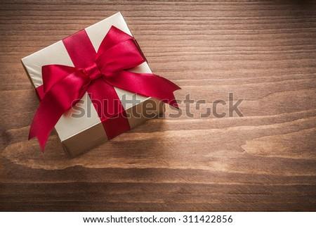 Glittery gold present box on vintage wooden board horizontal version. - stock photo