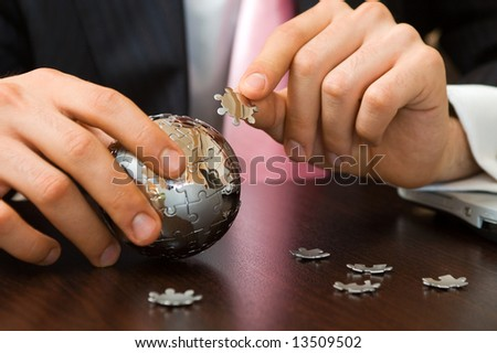 global business concept with a mini globe puzzle at the office - stock photo
