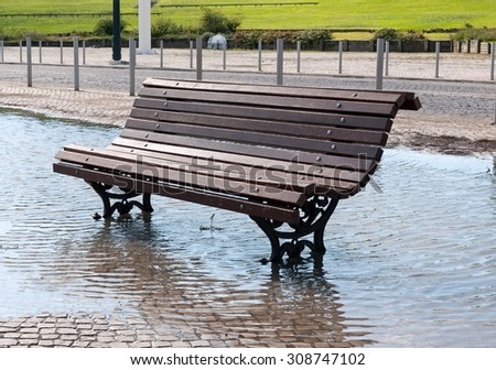 Global climate change - bench in a park flooded by heavy rain (photo taken in LIsbon, Portugal)