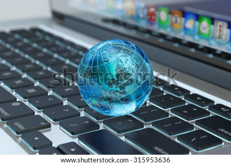 Global computer network communication, internet business and marketing concept, blue transparent Earth globe on laptop keyboard macro view (Elements of this image furnished by NASA) - stock photo