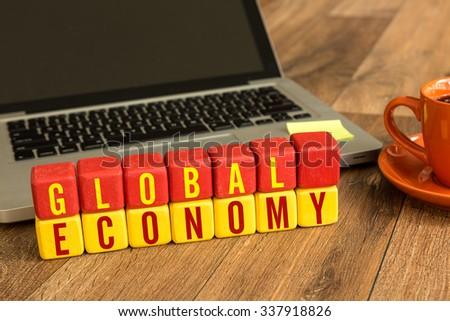 Global Economy written on a wooden cube in office desk - stock photo