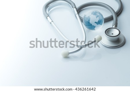 Global healthcare. Globe and stethoscope blue tone on white background