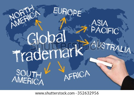 Global Trademark - blue chalkboard with female hand and text and world map in the background - stock photo