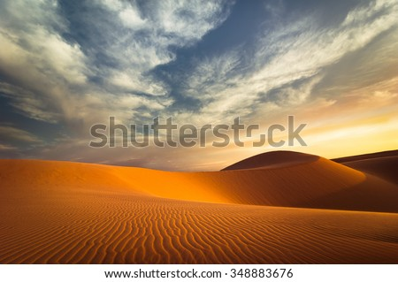 Global warming concept. Lonely sand dunes under dramatic evening sunset sky at drought  desert landscape - stock photo